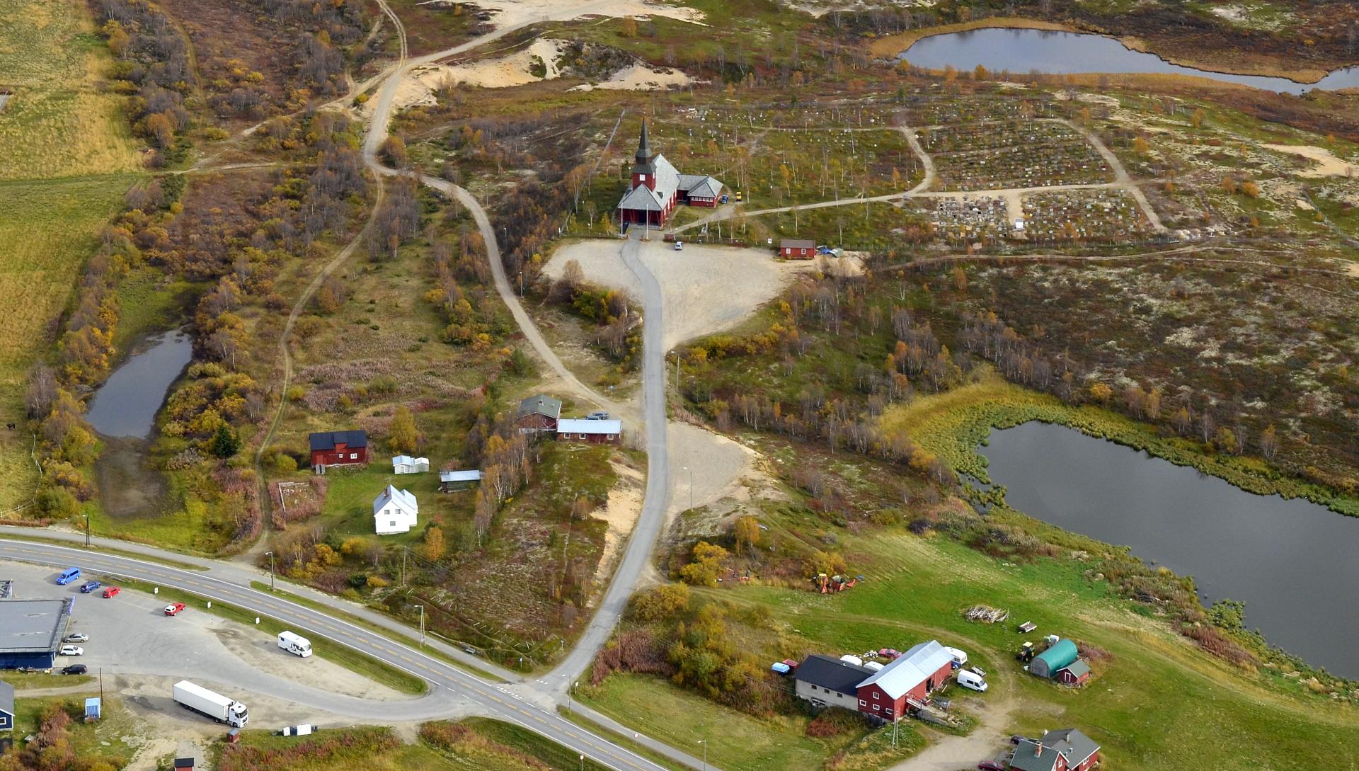 Kirkko ja hautausmaa keskellä kylää.