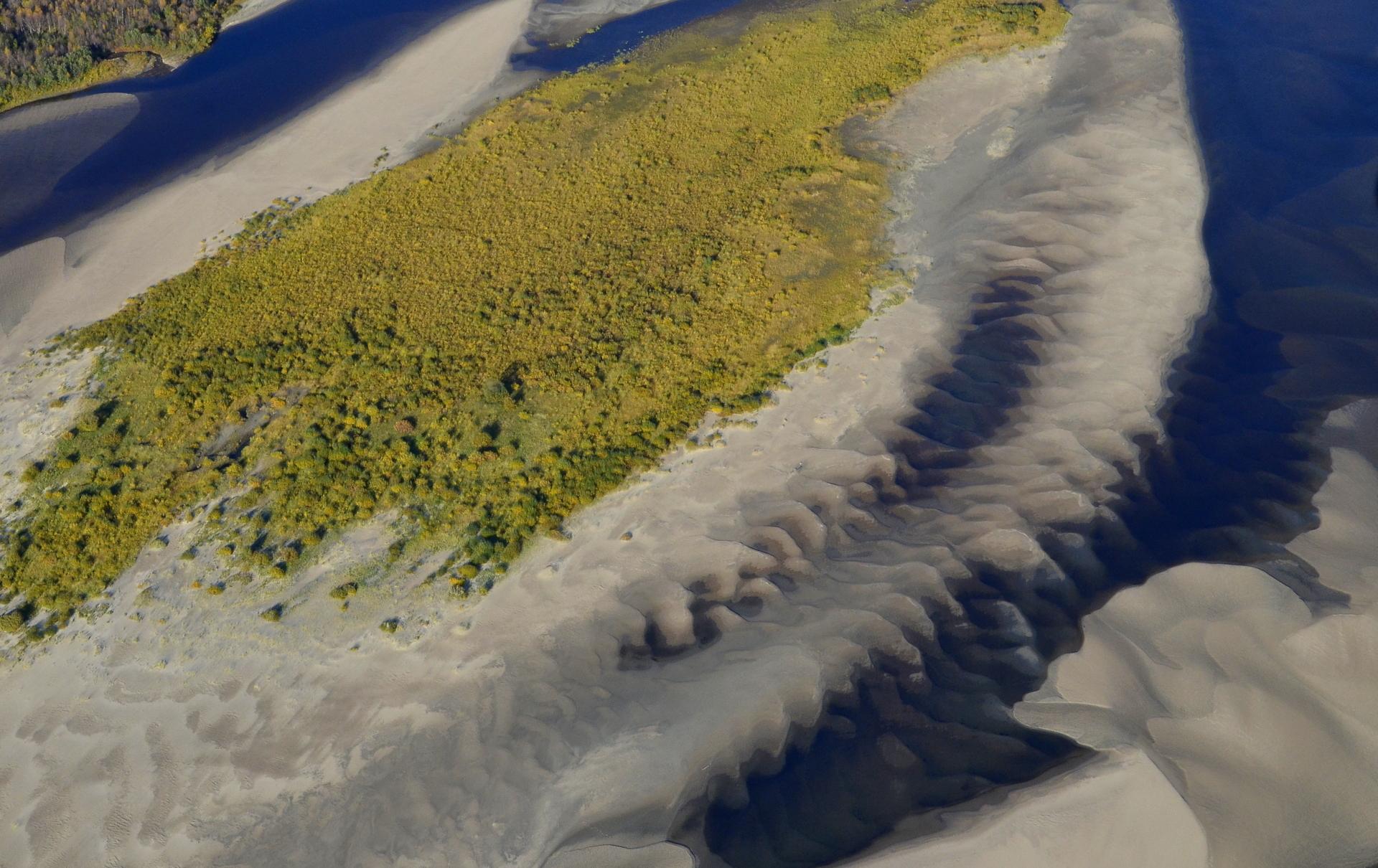 Virtaava vesi muotoilee joen pohjan hiekkaa.
