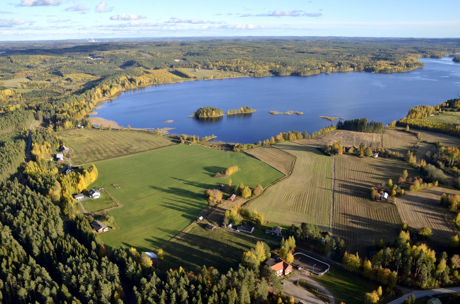 Kuvassa Lannevesi ja saman niminen järvi. Järven takana pellon laidassa suunistuksissa kisakeskuksena toimiva Voiniemen tila.