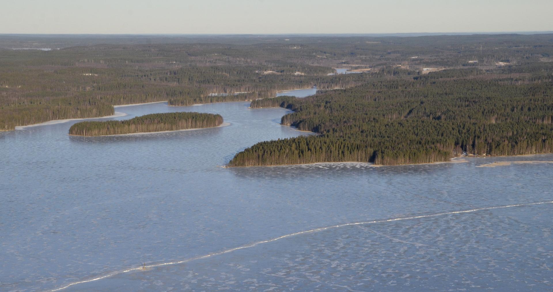 Leppiniemi, sen takana Kajamanlahti. Kalaniemen taajama siintää peltoineen taaempana.