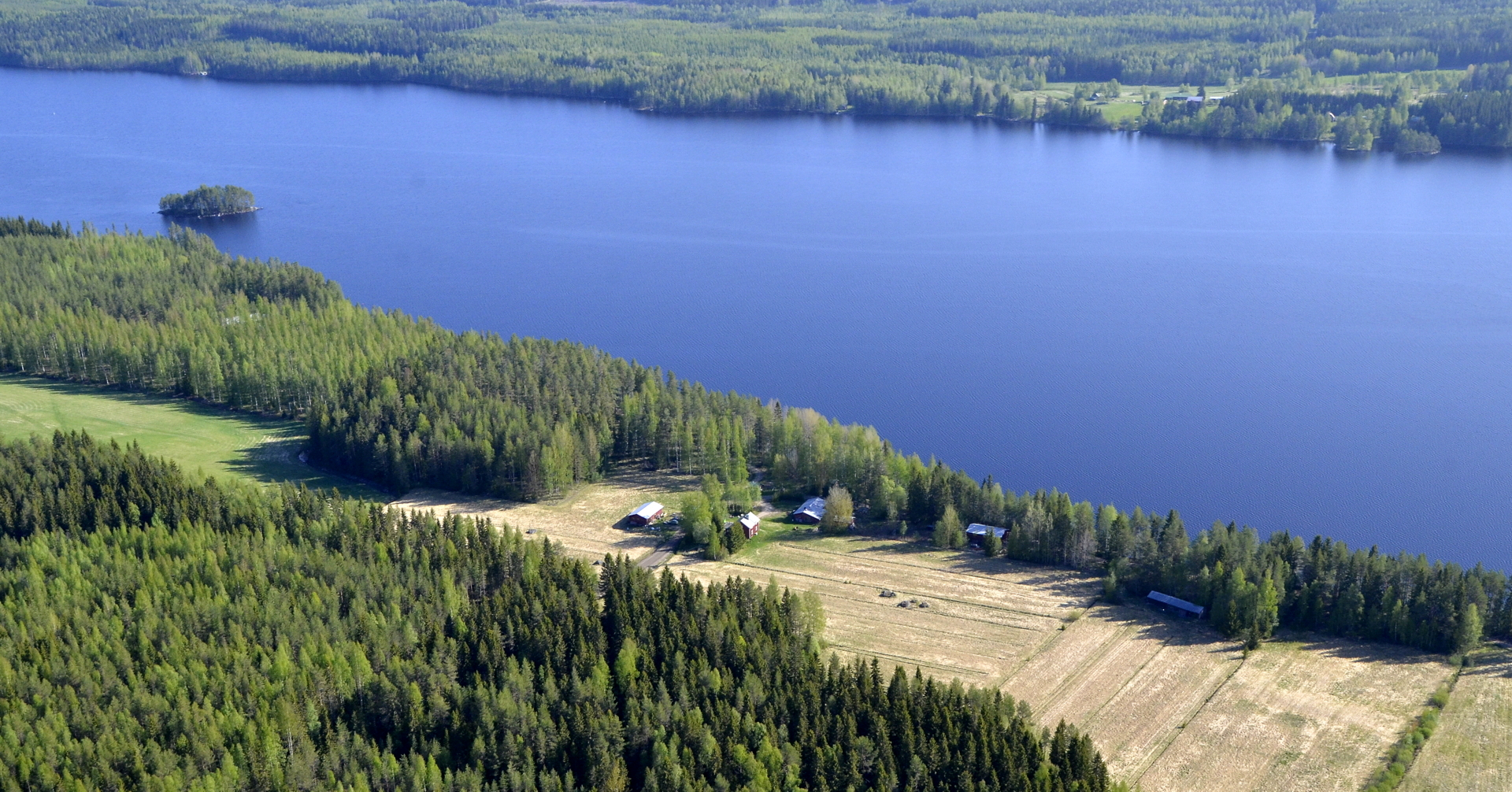 Vasemmalla Tolpansaari ja veden takarannalla Purala. Tila rannalla on Piilola.