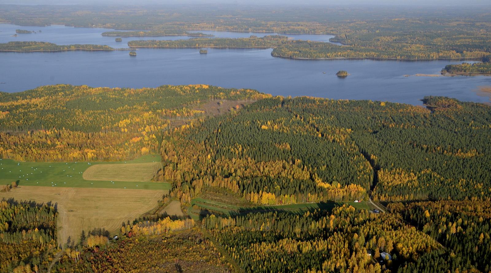 Siellä lentokenttä jo näkyykin kuvan oikeassa laidassa. Vuosjärvi taustalla ja sen takalaidalla oikealla Vuorilahti.